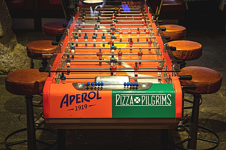 Pizza Playground *Pizza Pilgrims presents the perfect space for hire:*  The venue lies right opposite Canary Wharf and has a dedicated events space called the Pizza Playground. This is downstairs in the retro basement, which is equipped with the largest foosball table in London, a vintage pinball machine, SNES console from the 1990's and a more up to date Nintendo Switch with Mario Kart, Just Dance, Lets Sing and Mario Super Party available and plenty of board games to keep your guests entertained!  This Space has a fully functioning bar, Apple TV is also available for screenshare, presentations or even film screening and speakers allowing you to play your own music. This area can be hired exclusively or as a semi-private hire.  For your next team celebration, think of Pizza Pilgrims West India Quay first!