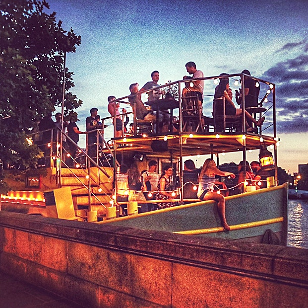 The Outside Stage Deck **Looking for an outside space on the river?**  The Outside Stage Deck, situated on the front of our converted 1930's Dutch Barge, offers great views of the city including the Houses of Parliament and the London Eye! It provides a more exclusive area for you and your Guests to enjoy your occasion.   Hire fees to start from £395 and for those with more of a budget we have minimum spend options also. Please note that hire fees and minimum spends differ depending on the time and day.