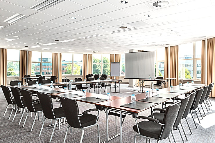 Lily + Iris Meeting rooms Lily and Iris can be combined into one meeting space. This meeting area is suitable for different types of meetings, from a conference to a network event and private dinner. Those meeting rooms are situated on the first floor and you can host up to 60 people.   The surface of this space is 104m2 and the ceiling height is 2.90 meters. The room is equipped with air conditioning, free Wi-Fi, a projector, presentation case and high quality furniture. It has a carpeted floor, variable walls and lots of natural daylight Furthermore, you can make use of our high speed internet for a small compensation.   Special Meeting & Events services: Our Event Planner will work closely together with you in order to plan the right menu for your special event and to meet your needs and wishes. Additionally, we offer you audio-visual equipment rental.   About NH Zoetermeer: The hotel is easy accessible by public transport and by car. It is just a 15 minutes' drive away from the bigger cities The Hague and Rotterdam. There is an on-site parking area, price €10,- per car, per day. In total, there are 14 meeting rooms. On the 7th floor you will find the hotel's gym (free of charge). Our modern Venti Bar is located next to the lobby. Other services that NH Zoetermeer offers are catering services, dry cleaning service, laundry service and a wake-up service. Furthermore, the hotel is wheelchair accessible.   Feel Safe at NH: NH Hotel Group launched Feel Safe at NH in collaboration with the SGS. As part of this, 10 protocols have been established for the safety of guests, participants and employees. With this, we guarantee that you can organize your meeting or event in all health and safety. Our F&B services are also adapted to the current situation.   The loaded meeting room capacity is the standard one. In case that any COVID restriction or regulation applies to your request, the selected hotel will apply the corresponding restrictions during the quotation process. B