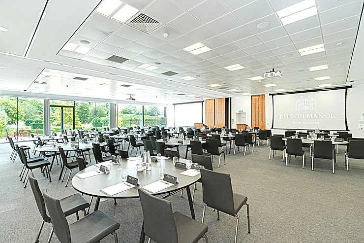 Auditorium  **Within the stunning modern Southgate Conference Centre building is the Auditorium.**  This fully flexible contemporary event Space can accommodate 330 people in a theatre layout, 174 cabaret style or 249 for a banquet.   Your eyes are drawn to the floor to ceiling windows covering one wall that overlooks a private decked terrace area, perfect for BBQ's, drinks receptions and enjoyed by all during meeting breaks.   The terrace leads to a wild flower garden and mini orchard and make you feel you are deep in the countryside, not 5 miles from Heathrow, 2.6 miles from Slough and just 3 minutes from J5 of M4/ 5 minutes from J15 M25.  The Auditorium is also very unique as it is able to be split into 2 rooms with their own entrances and own AV within them.   The conference centre building also has 4 additional light and bright meeting and training rooms and a large breakout area with tea/coffee facilities making the Southgate ideal for exclusive use.   The Southgate conference centre at Ditton Manor is located within 55 acres of grounds in a secure estate and surrounded by centuries old moat.