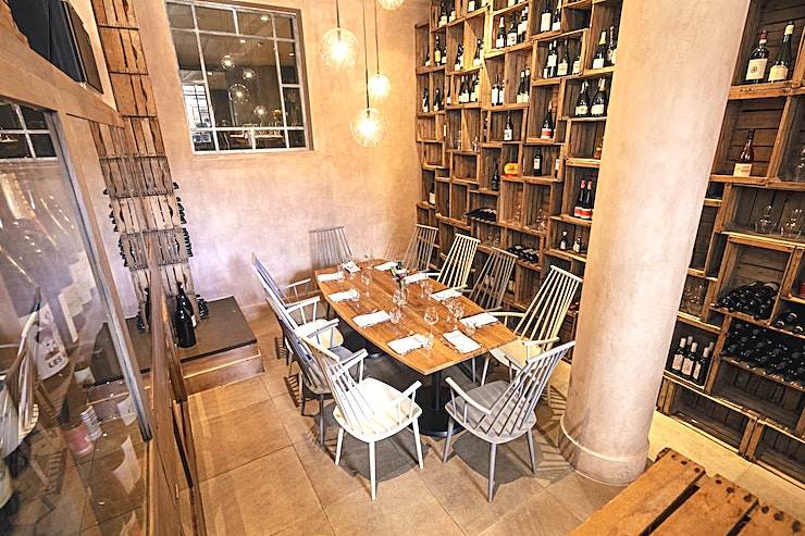 Wine Room **The cosy Wine Room has a real wow factor, with a wall adorned with rustic wooden wine shelves and polished metal surfaces contrasted with welcoming warm amber lighting.** 