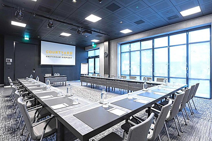 Meeting Room 8 **Meeting Room 8 at Courtyard by Marriott Amsterdam Airport is a top of the range meeting room for hire in Amsterdam.**  As well as business as leisure guests, experience in the 4-star hotel a luxurious ambience best described as casual, comfortable and efficient. Courtyard hotel has 260 modern rooms equipped with air conditioning, complimentary Wi-Fi, Smart TVs with Chromecast streaming (for wireless streaming) and spacious bathrooms.   Furthermore, there are 10 multipurpose meeting rooms, among which an auditorium with capacity up to 330 persons.   Each meeting room is equipped with whitewall, Click Share system and Marriott's Service App.