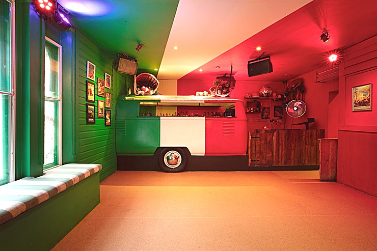 """L'Attico **It's party time all year round in the Attico, on the top floor of Bunga Bunga.**   A """"subtle"""" homage to the Italian flag adorns the walls and ceiling, to enhance the relaxed 60s vibe, and they've converted a Volkwagon Combivan into your very own private bar.    Capture your memories of the event in a hidden photo booth, available for your complimentary use.  Dining options are varied, for groups of 25 or less they can offer a seated dinner. The kitchen can prepare delicious salads and antipasto platters, or enjoy a famous Metro Pizzas- choose up to three different flavours to create 1 metre of delicious hot pizza, with extensive Vegan and Gluten-Free options.   If you'd prefer to host a cocktail party for up to 40 people, you can select from a canapé or buffet menu. They can also host one of their notorious Bunga Party brunches (with an optional Bottomless Bellini add-on) just for you and your Guests.   Order directly from the CombiBar during your event, or if you'd prefer to pre-order we can create bespoke drinks packages to suit your budget.    The Attico features its own Private Karaoke System, and they can also provide additional entertainment including DJs and live acts: Magicians, Drag Queens, or Burlesque for example.   On Fridays & Saturdays (except in the case of extended private hire) Club Bunga, on the floor below, opens to the public at 10.30pm. You and your Guests are welcome to stay and enjoy the rest of your night with as their DJ will be playing until 2am!"""