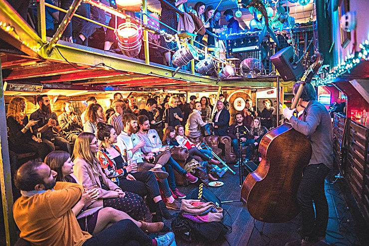 The Lower Deck **Tamesis Dock is an affordable, unique and quirky space to rent for private parties and events in London.**  Tamesis is a converted 1930s Dutch barge, moored permanently between Lambeth and Vauxhall Bridge, and now used as a floating pub, live music and events space perfect for coorporate events and large parties of up to 100. If you are looking for something completely original, with a laid-back feel, Tamesis could be the perfect place.   This party venue in central London is open daily throughout the year and does food, drink and weekend brunches. The kitchen is open until 10pm. Free WiFi is provided in the venue. Please note this space fee is based on a venue hire. Please select full day hire as the venue does not work to an hourly rate.