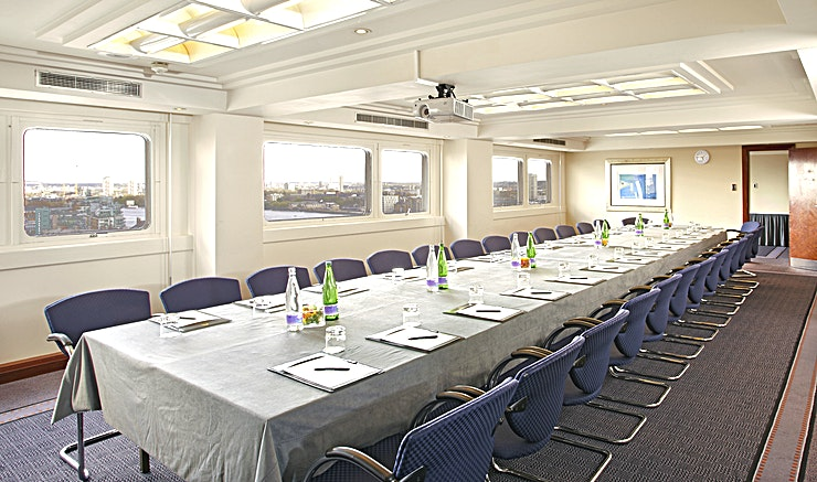Britannia Suite **For a board meeting Space that accommodates all your needs, The Tower Hotel has the meeting room hire for you**  The Britannia Suite is able to take up to 30 Guests in a boardroom style layout, enabling lively company discussions in a quiet, private location.   Featuring large windows that allow for plenty of natural daylight, this Space also provides Guests with the iconic view of London's skyline.  The Britannia Suite includes air-conditioning and assistance from a dedicated event Host, sure to accommodate all of your event requirements.   The Tower Hotel offers complimentary WI-FI, pens, pads & sweets on the table as well as projector and flip-chart, supplying everything you might need for a small company event.  With the added choice to arrange tea, coffee and snacks as well as lunch, this Space ensures your event remains relaxed and comfortable throughout.   This meeting room also has an adjoining room, Q, used for private catering facilities. Everything you'll need for team meetings and small conferences is right here in the Britannia Suite.