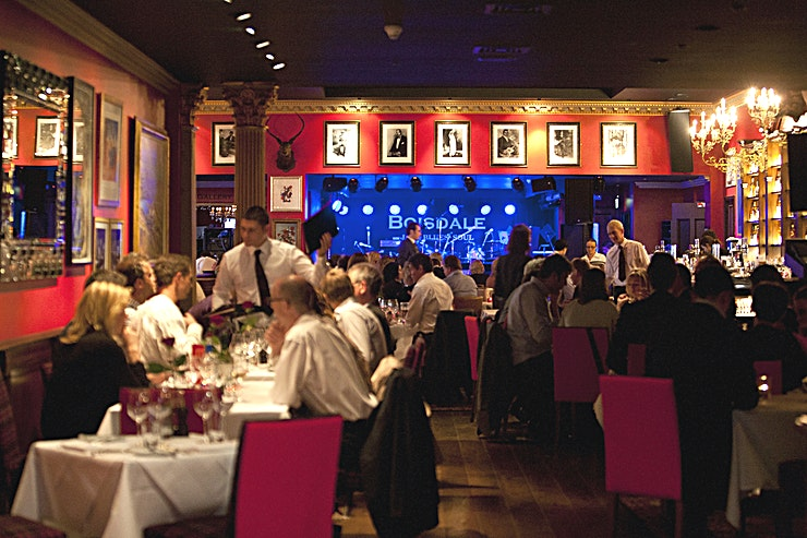 Restaurant & Jazz Club **The Restaurant & Jazz Club at Boisdale Canary Wharf is a stunning private party venue for hire in Canary Wharf.**  The venue is in Canary Wharf, just moments away from Canary Wharf station.   Boisdale of Canary Wharf occupies the entire façade of the 1st and 2nd floors of Cabot Hall overlooking the fountains of Cabot Square with uninterrupted views to City of London skyline.   This spectacular venue measures an impressive 12,000 square feet.   The restaurant is set on the second floor of a Gotham City-style Art Deco building overlooking the fountains in Cabot Square.   There are fantastic views overlooking the City of London skyline, making the restaurant is one of the most majestic premises to have opened in Canary Wharf in recent years.   The venue bears the distinctive Boisdale design of lacquer red and dark green walls, rich mahogany panelling, with an eclectic collection of classical and modern original artwork.   The restaurant has the ability to seat up to 200 guests and a world-class sound and stage system.   It is available as a private party hire for weddings, anniversaries and celebrations, as well as corporate events at no extra cost on Sundays.   During the week parts of the restaurant can be closed off to host private events for up to 40 Guests.  This stunning venue in Canary Wharf is one that is sure to impress your Guests.