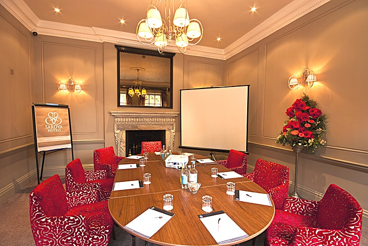 Sienna Room **Hire the Sienna Room at the Sir Christopher Wren Hotel for your next venue hire in London for corporate events.**   A beautiful suite flooded with natural daylight, the Sienna Room is ideal for boardroom meetings or private dining venue hire for up to 12 guests. It is even suitable for intimate civil ceremonies for up to 18 guests. Filled with comfortable seating, air conditioning and complimentary WiFi access making the Sienna Room the ideal location for executive meeting room hire in London.   **Sienna Room amenities:** • Complimentary WiFi • Natural daylight • Air conditioning • Blackout curtains • LCD projector • Screen • Flipchart • Stationery • Still and sparkling water • Tea, coffee and refreshments • Sweets / confectionery • Civil ceremony licence • Flexible seating arrangements • Telephone