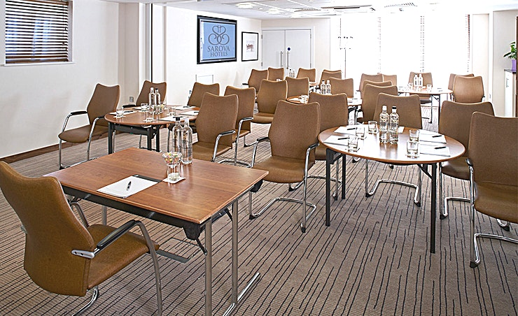 Buckingham Suite This contemporary conference room seats 65 theatre style or 24 in a classroom, u-shape or cabaret configuration. For board meetings or smaller seminars, the suite can be seperated into Buckingham 1 and Buckingham 2 with a soundproof partition.   **Features:** • Complimentary WiFi • Natural daylight • Air conditioning • Built in plasma screen • Flipchart • Stationery • Still and sparkling water • Tea, coffee and refreshments • Sweets and confectionery • Access to breakout area • Telephone • Contemporary lighting • Flexible seating arrangements