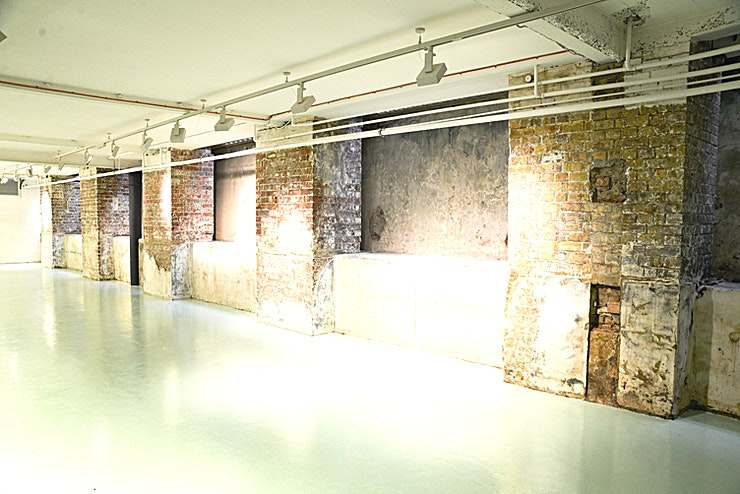 Alex Eagle Event Space The event space is situated on the lower ground floor of Alex Eagle Studio in the heart of Soho and comprises of a space covering approximately 100 sqm, two toilets and a foyer.   It can hold up to 150 people (standing) and is suitable for exhibitions, presentations, trade and fashion shows, film and photo shoots, press days, launches and so much more.  The floor is made from a clear blue resin and exposed brick work alcoves line one side of the room with white brick covering the opposite wall. The space is both neutral and very impactful with adjustable spotlights lining the ceiling to create whatever mood is required.