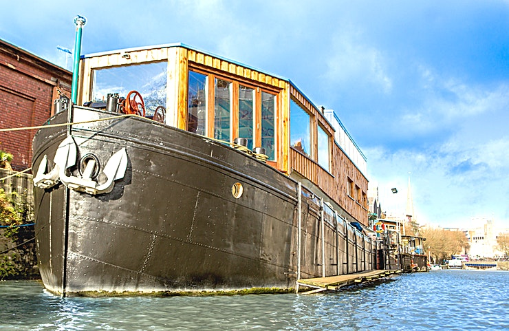 The Bridge **If you're looking for inspiration, this quirky and original Space will surely enhance some creativity in your next meeting**  The Bridge is one of two Spaces available to hire on board this 11ft steel dutch barge.  Floating Harbour Studios is nestled in the heart of Bristol's historic harbour. The top deck room boasts private access, allowing Guests a quiet location for brainstorming or workshops.  The Bridge features a walnut floor, historic map decor and an expansive river view through large windows that allow for an abundance of natural light.   This Space is perfect for any type of small-scale event including business meetings, workshops, conferences and presentations.  The room also has a little 'stage' ideal for presentations or for elevating the whiteboard or screen. This Space also includes beautiful steel and reclaimed wood custom-made conference tables that seat up to 14 Guests in a boardroom style.  The venue can accommodate for extra Guests by adding an extra table to seat 24 Guests in a cabaret style.   If you'd like a blank canvas, Floating Harbour Studios can remove all the furniture for you to hold a class or a workshop for up to 30 Guests.  Versatile and effective, The Bridge at Floating Harbour Studios presents an unconventional yet creative option for meeting room hire in Bristol.