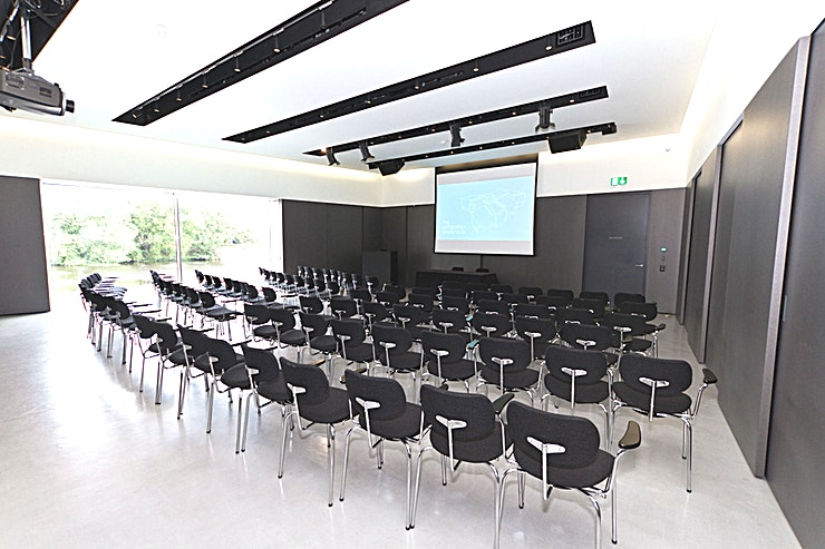 Auditorium  Our elegant, purpose-built auditorium is a modern space located off the main foyer area of the gallery. It offers flexibility and comfort for a variety of events and is fully fitted with Wi-Fi and extensive audio-visual facilities including large screen, integrated projector and free standing lectern. The expansive window provides you with breath-taking views of the River Calder.   The Auditorium is a versatile space that can be transformed for all events. It is perfect for conferences, team away days, private dining, launch parties and many more! This is an ideal venue for a variety of occasions.   Available to hire seven days-a-week including evenings. Holds up to 100 people theatre-style or up to 90 for dining.