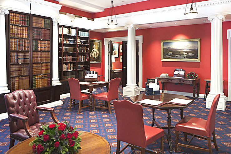 The Library **Surrounded in classical literature, your Guests will feel inspired by The Library at The Caledonian Club**  The Library is situated on the ground floor, with its magnificent panelling and elegant book-lined shelves is suitable for cocktail parties, dinners and lunches.   The two adjoining rooms, The Bowmore and Card rooms can be used as a separate bar or buffet area, creating a versatile event Space for larger corporate events.  The rich decor is enhanced by outstanding portraiture. This Space is designed with sophistication in mind.   Ideal for meetings and private events alike, The Library provides a Space that can accommodate up to 60 Guests.  Iconic white pillars enrich the warm, red walls. A Space that is sure to impress.