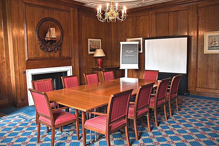 Churchill **Hire the Churchill room at De Vere Devonport House for a medium meeting to hire in the heart of Greenwich.**   In the centre of Greenwich and steeped in naval history is one of the best located hotels in Greenwich. De Vere Venues Devonport House offers you 99 bedrooms and 13 state-of-the-art meeting, training rooms and an amazing great outside space. There is 5 medium sized meeting rooms onsite where the capacities range from 14-26 boardroom style and are all filled with character and the original features.   The Churchill Room is a traditional setting with its oak-panelled walls for smaller meetings up to 30 guests.   Day Delegate Rates include: ·         Main training room ·         LCD projector & Screen ·         2 Course Restaurant Buffet or Working Lunch ·         2 Flipcharts ·         Delegate stationery (paper, pencils & place cards) ·         Trainer toolkit (post-its, wall tape, scissors, stapler, etc.) ·         Wi-Fi access ·         Unlimited tea, coffee, biscuits & whole fresh fruit ·         Chilled water dispenser (in the meeting room) ·         Power sockets for each delegates included