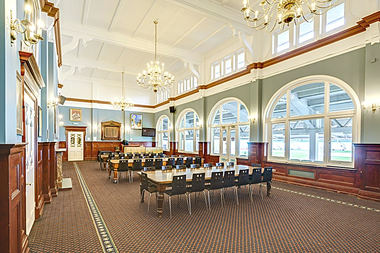 Long Room **The Long Room at the  Kia Oval Cricket Stadium is one of the best options for meeting room London has to offer. Perfect for your next corporate event.**   The Long Room is the most historic room within the Members Pavilion. Built in 1898, the room is steeped in history, with portraits of the Surrey greats adorning the walls. The huge windows and high ceiling allow for plenty of natural daylight and the doors lead out directly to the side of the pitch, so your guests can take their coffee breaks and lunches whilst taking in spectacular pitchside views. The room can accommodate a dinner for 80 guests, or can fit 100 guests theatre style.
