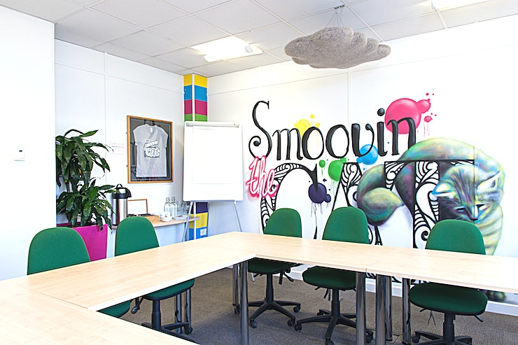 Smoovin the Cat **Welcome to Smoovin the Cat, one of several rooms contained within The Waterfront Offices. Set beside the river on central Bristol's Welsh Back, this meeting room's central location is second to none.**  Smoovin the Cat is a bright and funky space which is perfect for boardroom style meetings for up to 14 people. All rooms come with complimentary hot drinks and water, with your catering requirements managed by a superb local caterer. When booking, just let us know if you would like catering and we will contact you to discuss in more detail. The costs of room hire also include access to Wifi, audiovisual equipment, along with access to a large kitchen with free tea and coffee making facilities, ping pong table, eating area and sofas. Various other services such as printing and photocopying are also available.  **More details about the venue:**  The Waterfront meeting, conference and training rooms can be found on the 1st and 2nd floors of newly refurbished offices situated on Welsh Back in Central Bristol, with stunning views overlooking the floating harbour. A stone's throw from Bristol's City Centre, Queens Square and less than a 10-minute walk from Bristol Temple Meads Train Station - making these the most ideally located meeting rooms Bristol has to offer!   This space is dedicated to hosting an array of conference, meeting and training events of varying sizes, from a Board Room of 6, up to a training or meeting/conference room for 50 in a theatre style.   The floor has a funky Bristol feel, with photos and murals of Bristol's famous sites including the iconic Clifton suspension bridge, SS Great Britain and the colourful houses of Totterdown. Others murals reflect the room names, all of which are Bristol colloquial phrases from Brizzle to Gert Lush.   Accompanying the meeting rooms is access to a large fully equipped break out space including kitchen, sofas, space to eat and also a table tennis table. All of this surrounded by exceptional views o