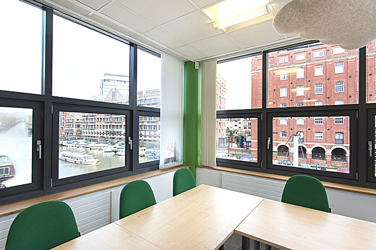 Babbers **Babbers is one of several rooms contained within The Waterfront Offices. Set beside the river on central Bristol's Welsh Back, this meeting room's central location is second to none.**  Babbers is a bright and funky space with windows overlooking the water on 2 sides. This room is perfect for boardroom style meetings for up to 10 people. All rooms come with complimentary hot drinks and water, with any catering requirements managed by a superb local caterer. When booking, just let us know if you would like catering and we will contact you to discuss in more detail. The costs of room hire also include access to Wifi, audiovisual equipment, along with access to a large kitchen with free tea and coffee making facilities, ping pong table, eating area and sofas. Various other services such as printing and photocopying are also available.  **More details about the venue:**  The Waterfront meeting, conference and training rooms can be found on the 1st and 2nd floors of newly refurbished offices situated on Welsh Back in Central Bristol, with stunning views overlooking the floating harbour. A stone's throw from Bristol's City Centre, Queens Square and less than a 10-minute walk from Bristol Temple Meads Train Station - making these the most ideally located meeting rooms Bristol has to offer!   The space is dedicated to hosting an array of conference, meeting and training events of varying sizes, from a Board Room of 6, up to a training or meeting/conference room for 50 in a theatre style.   The floor has a funky Bristol feel, with photos and murals of Bristol's famous sites including the iconic Clifton suspension bridge, SS Great Britain and the colourful houses of Totterdown. Others murals reflect the room names, all of which are Bristol colloquial phrases from Brizzle to Gert Lush.   Accompanying the meeting rooms is access to a large fully equipped break out space including kitchen, sofas, space to eat and also a table tennis table. All of this surrounded by exc
