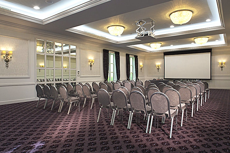 The Brunel Suite **Welcome to the Brunel Suite at the Bailbrook House Hotel in Somerset.**   Located on the ground floor of Bailbrook Court, the Brunel Suite is the largest function space and offers its own entrance and registration foyer, private bar and atrium.  It is ideal for conference venue hire, Somerset meeting rooms, training days, large events, theatre style presentations or private dinners. With a capacity of up to 160 it is a very versatile and attractive space with lots of natural daylight and has a light and airy feel, complete with patio style doors to its own outside area.  It also features a very large ceiling drop down screen with surround sound for presentations, video footage or we access via the free WiFi,