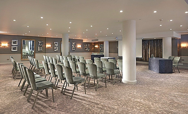 Richmond **Newly refurbished modern style room, the Richmond room at the Richmond Hill Hotel is one of the best options for venue hire outside of London!**  With a raised area with private bar and adjoining sun terrace, the Richmond room is then situated in the centre of the hotel and on the lower ground floor. There are flexible lighting concepts catering for event theming making it more than suitable for meetings and banqueting events. With four adjacent syndicate rooms for group work and a max capacity of 100 delegates for a theatre style. Richmond Hill Hotel has one of the best options for venue hire Surrey has to offer!