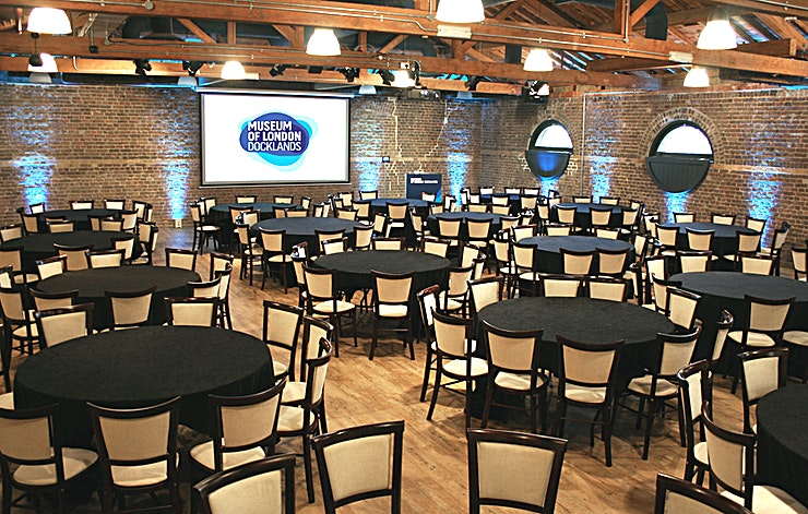 Wilberforce Room **The newly-refurbished flexible Wilberforce Room at the Museum of London Docklands is a unique option for venue hire in London!**   The Wilberforce Room at the Museum of London Docklands has a max capacity for up to seated 273 guests, and with state of the art audio-visual facilities and a blackout option, it is perfect for conferences and presentations in London.   Perfect for a whole variety of different events, from dinners to parties, the Wilberforce Room at the iconic Museum of London Docklands has all of the unique charms of a 19th-century warehouse, whilst being brought right up to date with a state of the art audio-visual system.   As part of Conference News' Meet Out to Help Out initiative, we're offering 20% off meeting room hire for events booked at the Museum of London in October 2020 – February 2021.