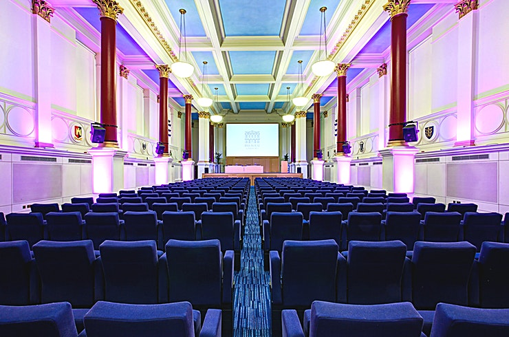 Great Hall **Hire the Great Hall at the BMA House for one of the best options for conference venue hire London has to offer. Perfect for a wide range of different events.**   The Great Hall is the flagship room of BMA House and is perfect for Conferences, AGMs, Award Ceremonies and Dinners; it is also licensed for Wedding Ceremonies!   Located on the first floor, in the centre of the House, this majestic 28-foot high room features floor to ceiling Corinthian columns, decorated with painted gold leaf.    The high-level windows inject an abundance of natural daylight, yet full blackout facilities are available if required.    The room has an impressive stage perfect for presenting from and conducting Awards events.  The Great Hall benefits from retractable seating swiftly transforming it from a theatre style room to a multi-purpose space which can be set cabaret, classroom or dinner style.    The Great Hall boasts an array of Audio Visual equipment supported by the on-site team.  Two small balconies look out over the stunning memorial Courtyard and provide a perfect vantage point for photographers wanting to capture large group shots.