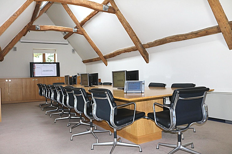Boardroom **Need a boardroom to hire in Bristol? Welcome to the Old Church Farm Conference Centre.**  The boardroom seats 18 people around a bespoke table equipped with 6 monitors which are synchronised with the main 60-inch plasma display that rises from the rear cupboards on hydraulic rams. There are AV and power sockets along the centre of the table and remote controlled blinds, windows and dimmable lighting. Extra comfort is provided by air conditioning. A breakout area outside the room houses a fridge for chilled drinks.  Old Church Farm conference centre is conveniently located just 6 minutes from the M4/M5 interchange north of Bristol. It was converted from a historic barn by Rolls Royce PLC who owned the property with its adjacent manor house and church ruin from 1950 until 2017.  The conference centre comprises an 18 seater boardroom, two twelve seater meeting rooms (that can be rearranged as training rooms etc) and a function room with skittle alley! Refreshments are provided by the AA 5 Star Gold Award guest house (Old Church Farm) which has seven luxury ensuite bedrooms should delegates need to stay. Old Church Farm also has two dining rooms for formal and informal dining as well as a 38-foot drawing room.  There is ample free parking on the 9-acre site and beautiful gardens overlooking South Gloucestershire countryside. Fibre internet provides good connectivity to online resources.
