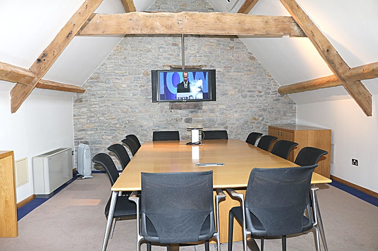 Meeting Room 2 **Need a meeting room to hire in Bristol? Welcome to Meeting Room 2 at the Old Church Farm Conference Centre.**   Meeting Room 2 at Old Church Farm conference centre is ideal for 12 delegates seated around a large table (four along the long sides and two at each end). The desk has pop-up power and AV connections for the 55 inch Panasonic wall-mounted screen and speakers. There is WiFi and Wired internet access, natural daylight through remotely operated Velux Windows (also with remote controlled blinds) and dimmable lighting. Outside the room is a breakout area with a fridge for chilled drinks.  Old Church Farm conference centre is 6 minutes from the M4/M5 interchange just north of Bristol. In addition to this meeting room, there is a further meeting room, a boardroom and a large function room with skittle alley. Old Church Farm conference centre is conveniently located just 6 minutes from the M4/M5 interchange north of Bristol. It was converted from a historic barn by Rolls Royce PLC who owned the property with its adjacent manor house and church ruin from 1950 until 2017.  The conference centre comprises an 18 seater boardroom, two twelve seater meeting rooms (that can be rearranged as training rooms etc) and a function room with skittle alley! Refreshments are provided by the AA 5 Star Gold Award guest house (Old Church Farm) which has seven luxury ensuite bedrooms should delegates need to stay. Old Church Farm also has two dining rooms for formal and informal dining as well as a 38-foot drawing room.  There is ample free parking on the 9-acre site and beautiful gardens overlooking South Gloucestershire countryside. Fibre internet provides good connectivity to online resources.