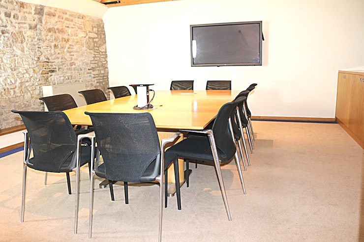 Meeting Room 1 **Meeting Room 1 at Old Church Farm conference centre is ideal for 12 delegates seated around a large table.**  The desk has pop-up power and AV connections for the 60 inch Panasonic wall-mounted screen and speakers. There is WiFi and Wired internet access, natural daylight through remotely operated Velux Windows (also with remote controlled blinds) and dimmable lighting. Outside the room is a breakout area with a fridge for chilled drinks.  Old Church Farm conference centre is 6 minutes from the M4/M5 interchange just north of Bristol. In addition to this meeting room, there is a further meeting room, a boardroom and a large function room with skittle alley. Old Church Farm conference centre is conveniently located just 6 minutes from the M4/M5 interchange north of Bristol. It was converted from a historic barn by Rolls Royce PLC who owned the property with its adjacent manor house and church ruin from 1950 until 2017.  The conference centre comprises an 18 seater boardroom, two twelve seater meeting rooms (that can be rearranged as training rooms etc) and a function room with skittle alley! Refreshments are provided by the AA 5 Star Gold Award guest house (Old Church Farm) which has seven luxury ensuite bedrooms should delegates need to stay. Old Church Farm also has two dining rooms for formal and informal dining as well as a 38-foot drawing room.  There is ample free parking on the 9-acre site and beautiful gardens overlooking South Gloucestershire countryside. Fibre internet provides good connectivity to online resources.