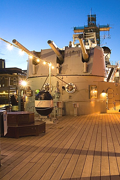 The Quarter Deck  **The large and beautiful Quarterdeck on the HMS Belfast, an outstanding space for a large event of up to 200 guests.**   There can surely be no finer vista for an evening reception than standing on the Quarter Deck, looking out at Tower Bridge, the Tower of London and the Thames dockland scenes. Between London's most iconic landmarks there is no better place to spend a summer evening than The Quarter Deck.  The beautifully appointed wooden decking, that, during her commissioned years, played host to only the Officers of HMS Belfast, makes this period setting one of the finest in London and the ideal space for your summer events.