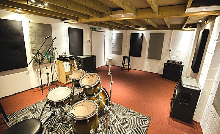 Studio 2 **For a Space suited specifically for bands and creative musicians, Reading's Rhoom Studios has the Space for you**  This Space is the second-largest of the four studios. Measuring 32.5 square metres, Studio 2 is perfect for bands with 3 to 6 members. Whether it's an intimate meeting you require or a sound-blasting band session. The Rhoom Studios has got you covered.  This Space is available 7 days a week, from 8am to 11pm. If you're an early riser, this Space is the ideal recording destination for you. With The Castle Inn and The Warren supplying pubs nearby, your recording session can end with a well-deserved drink.  During its 2017 renovation, Studio 2 acquired an abundance of new equipment. It is now superbly accommodating for all your musical needs.  Studio 2 hire includes: Five-piece drum kit Two 4x12 guitar cabs A bass amp  Two microphones.  With cymbals, guitar amps and extra mics available on request.  Free parking, tea, coffee and comfortable seating provided. This is the ideal creative Space.