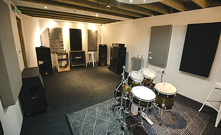 Studio 3 **For a music recording studio with plenty of equipment and flexible hours, Studio 3 at The Rhoom Studios**  This Space is the third-largest of the four studios available at The Rhoom Studios. It measures 30 square metres, creating the perfect destination for bands with 3 to 6 members.   Open 24 hours, 7 days a week, Studio 3 is versatile in both space and availability. Whatever time you require, this Space can cater to your needs.   In 2017, the studio underwent a huge renovation. Adding acoustic diffusers and specialist sound-proofing to the walls. This year The Rhoom Studios installed a brand new powerful PA system. Allowing Guests to spend more time making music and less time as sound engineers.   Studio hire includes:  Five-piece drum kit  Two 4x12 guitar cabs A bass amp Two microphones.   Upon request, cymbals, guitar amps and extra mics are available. Equipping you with all with may need for your next rehearsal or recording session.  With comfortable seating and refreshments provided. You are assured to have a successful musical experience at Studio 3.