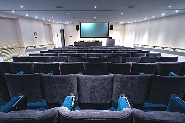 Godfrey Mitchell Theatre **Searching for a Space to host a conference, lecture or screening? One Great George Street has the Space for you**  Located on the lower ground floor of this exceptional Westminster event venue is the venue's second purpose-built, tiered lecture theatre, the Godfrey Mitchell Theatre.   The theatre is fully equipped with state-of-the art presentation technology. There is fixed raked seating for up to 106 Guests, including fully-accessible facilities and a front and rear entrance.   At the front is a speaker's lectern and top table for up to five people; each with fixed microphones.   These pieces of furniture can be removed if the occasion demands a different set up. The space is very minimalist and modern in style with soft blue and white; additional lighting can be incorporated to create a theme to your corporate event.  The Godfrey Mitchell Theatre is ideal for small conferences, presentations and lectures, offering all of the facilities you'll need for an efficient and effective event.  This Space is also ideal for seminars, product launches, press conferences and AGM's. Any corporate event is perfectly accommodated in this Westminster location.   This and the venue's larger Telford Theatre have the capability to be linked up internally which will allow for an in-house conference capacity of over 340 Guests.  One Great George Street offers an ideal option for event Space hire in the heart of Westminster.