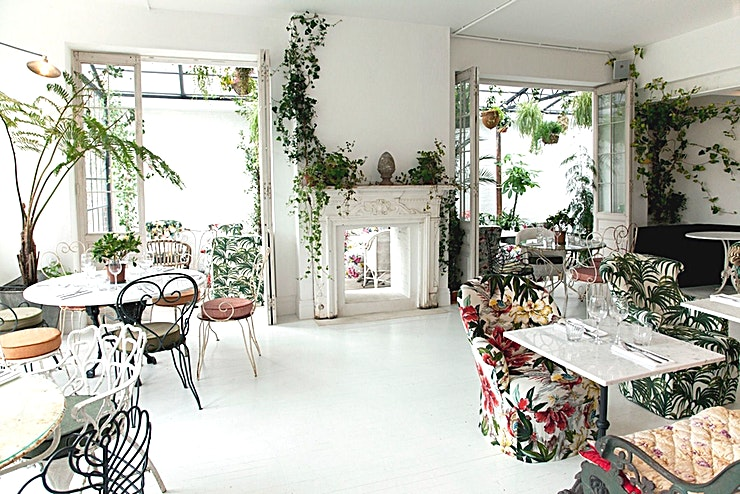 Garden Room **Hire the Garden Room at one of the best options for summer party venue hire at Bourne & Hollingsworth Buildings.**  Walk through the bar, past the Café, and you find yourself in the Garden Room, amongst a verdant expanse of greenery. Capturing the impression of an abandoned country house, where the gardens and state rooms have slowly grown into one another and gone to seed, the Garden Room makes up the largest restaurant space. Mixing soft furnishings and armchairs with cane garden furniture and wrought iron benches, the whole space is filled with hanging baskets, fully grown trees and trailing creepers, effectively bringing the outside in and offering a relaxed and charming dining experience. This room is a favourite for fashion events, lending itself perfectly to clothing collection exhibitions, beauty product launches and fashion shoots.   The design of Bourne & Hollingsworth Buildings was a collaboration between the in-house creative team, Lionel Real de Azua of Red Deer Architects and Louise Davies of Box 9 Architects creating one of the best options making this the perfect private dining room to hire in London. Purposefully moving away from the overthought and increasingly faddy designs that have flooded the London restaurant and bar scene in recent years, B&H Buildings features pared back, classic interiors that are light, clean and almost minimalist in their design.