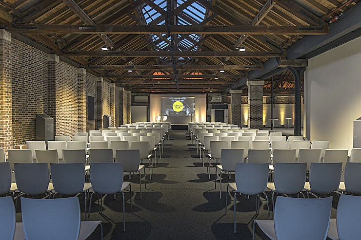 The Dock Gallery **Hire The Dock Gallery for your next corporate event hire in London.**  The Dock Gallery is the newest Space available to hire at Tobacco Dock.  Flooded with natural light and benefiting from Tobacco Dock's pared-back style the Space can be used for a range of corporate events.   Recently renovated, The Dock Gallery is a self-contained area with its own entrance, plus it is the only Space at Tobacco Dock available for comprehensive 'plug and play' hire.   Perfect for those looking for straightforward planning for an impressive conference or exhibition, this vast Space can accommodate up to 250 people.   Conveniently placed beside The Dock meeting rooms, you can incorporate these Spaces into your package as breakouts, workshop areas or meeting rooms.   With stunning views of the quayside, exposed brickwork and listed timber beams The Dock Gallery will leave your Guests with plenty to talk about.