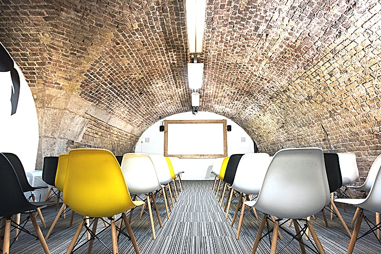 Kennedy **Hire Kennedy at Tobacco Dock for your next meeting room hire in London**   Just a 10 minute walk from Tower Bridge and with excellent access to the City, and Canary Wharf a meeting room hire at Tobacco Dock is an excellent choice.   Kennedy is an industrial meeting room, situated within one of the original arches of the dock, and equipped with a state of the art 75-inch plasma screen perfect for pitching or presenting.   Offering Space for meetings between 6 -120 Guests, meeting rooms at Tobacco Dock can be hired individually or combined dependent on your event needs.