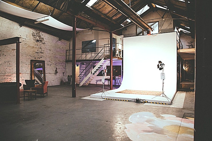 Studio A **Studio A at D-Light Studios is a unique Dublin studio for hire.**  Studio A is a large, dynamic Space filled with natural light. The original Belfast Iron pillars and pitched roof, cyclorama and changing room make this studio particularly suitable for photography.    A unique feature of this Space is the ramp which allows cars to be driven into the studio from street level - ideal for loading in and out heavy equipment.   In addition to photo shoots, this Space has hosted yoga classes, television commercials, exhibitions, corporate events, product launches and indoor markets.  D-Light Studios is housed in a 200-year-old converted, city centre warehouse. The studio is a large, industrial blank canvas for you to put your creative stamp on.   The studio primarily functions as a Photography and Filming location and co-working space. We have limited availability for events but are always open to proposals for creative uses of this huge, unique space.