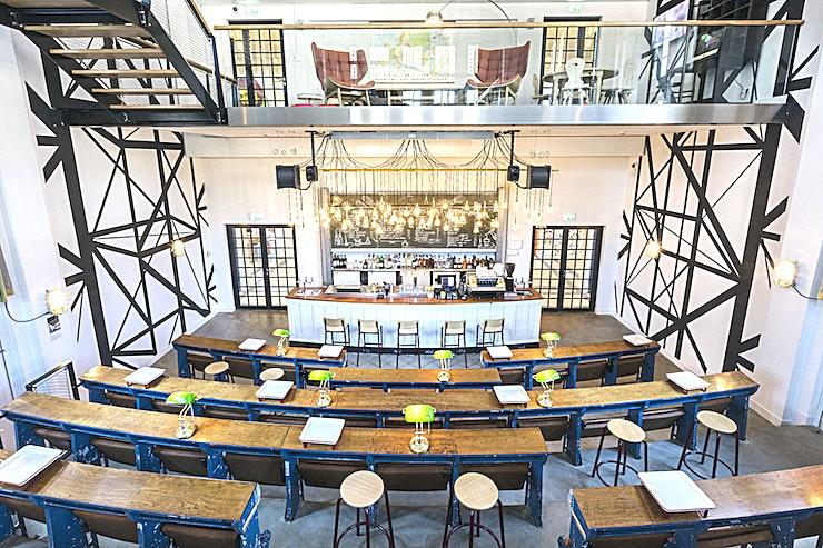 Auditorium **Nescio - Auditorium Bar is een dynamische locatie voor privé feestjes in Amsterdam.**  Dit is geen gewone bar, de voormalige collegezaal is omgebouwd tot een auditorium met een chill-out mezzanine die neerkijkt op de bar.   Deze ruimte is slim ontworpen door de zitplaatsen van het klaslokaal opnieuw te gebruiken, waardoor het een comfortabele stijl heeft gekregen die de nadruk legt op het sociale aspect van evenementen.