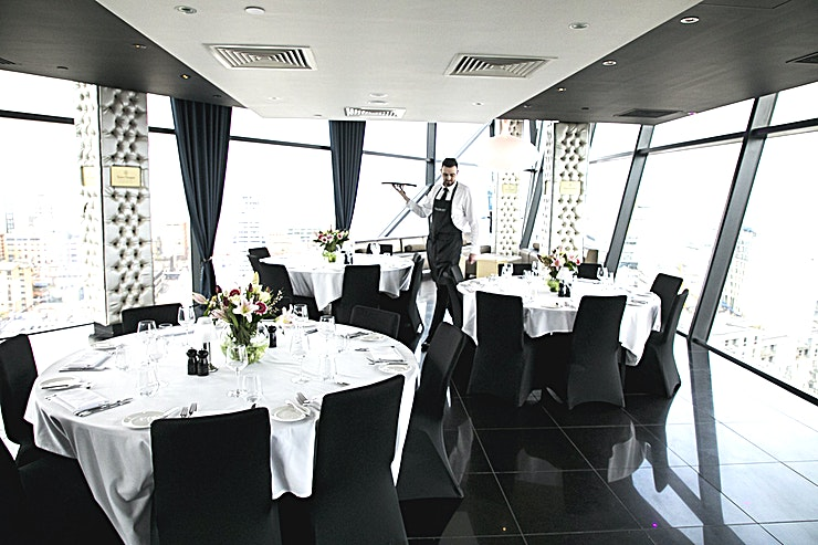 """Champagne Room **Champagne Room at Marco Pierre White at The Cube is a stylish private dining room for hire in Birmingham.**  Tucked away from the main bar & restaurant is the well-appointed Champagne Bar. This all-purpose room is specifically designed to host the most luxurious of parties, with a fully equipped bar, live music, dance floor and trademark views of the city.   The most popular destination with its stunning 360 degree views of Birmingham's City Skyline, impressive for those very important events, with friends or colleagues.   This is a venue that will definitely impress. Capable of seating up to 60 guests for a private lunch or dinner, or 120 for a more informal drinks reception.   Create a """"wow"""" factor for delegates and break away from the ordinary meeting room. Our Champagne Bar offers you lots of natural daylight along with everything you need for a stylish event.  Offering a variety of menu options for delegate breakfasts and lunches, this venue will have your guests talking about it for weeks after."""