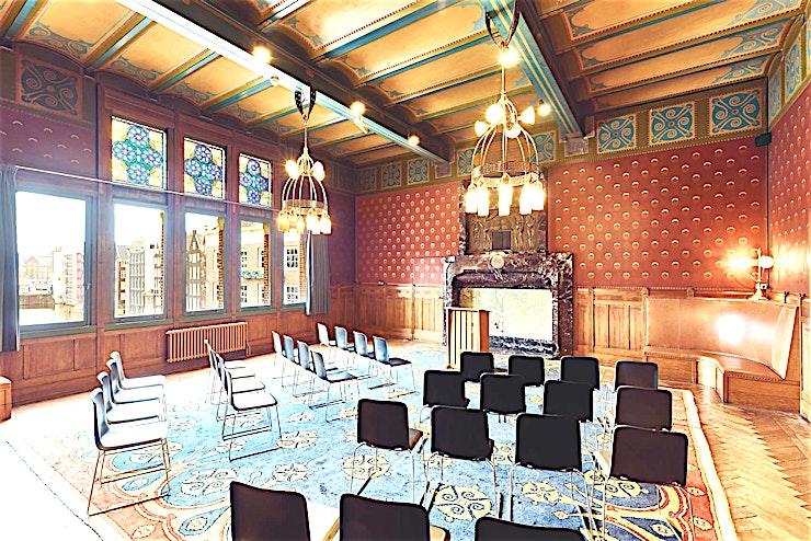 Directiekamer **Directiekamer is Meet Berlage's beste locatie te huur in Amsterdam.**  Deze grote historische zaal biedt niet alleen een prachtig zicht op het Centraal Station van Amsterdam, maar beschikt ook over veel kleine details over de geschiedenis van deze kamer en de locatie. Oorspronkelijk was deze kamer de vergaderzaal van de handelaren in de Amsterdam Stock Exchange, nu heeft u de mogelijkheid om deze kamer te gebruiken zoals u in gedachten heeft.  Afhankelijk van welke opstelling u kiest, kan deze kamer een intieme vergadering van 4 personen tot 60 personen in theateropstelling hosten.