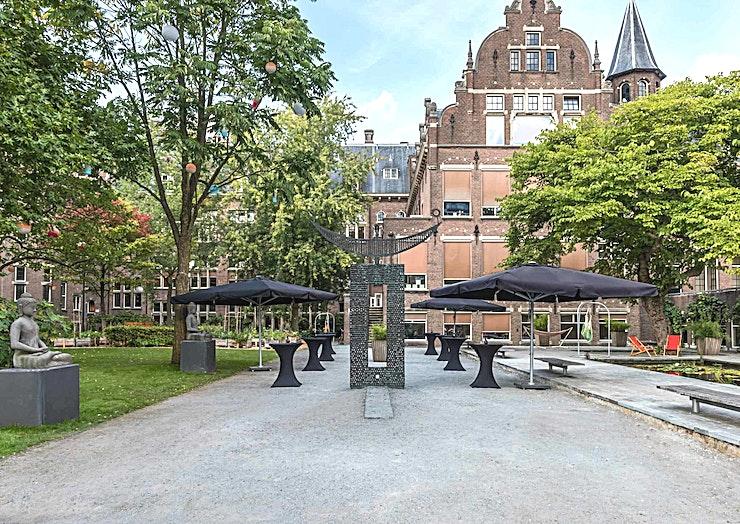 De Binnentuin **Het Courtyard in het KIT is een stijlvolle buitenruimte te huur in Amsterdam.**   KIT Koninklijk Instituut voor de Tropen is een onafhankelijk expertisecentrum gewijd aan onderwijs, interculturele samenwerking, gastvrijheid en duurzame ontwikkeling.    Op basis van een nationaal erfgoed in Amsterdam, KIT richt zich op belangrijke gebieden waar het een verschil kan maken: Geslacht, Global Health, Interculturele Communicatie en duurzame economische ontwikkeling.