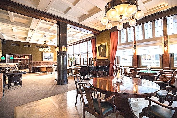 De Clubzaal en Bar **De Club Room en Bar van de Koninklijke Industrieele Groote Club is een prachtig privé feestlocatie te huur in Amsterdam.**  De vele kamers, elk met hun karakteristieke sfeer, lenen zich uitstekend voor diverse evenementen. Welk evenement je ook organiseert, dit monumentale gebouw, met een klassiek moderne en mystieke sfeer, biedt de perfecte ervaring.  Voeg daar servicegericht en competente medewerkers van de locatie aan toe en bent u verzekerd van een onvergetelijke dag.  De Club heeft acht kamers, waaronder een restaurant, bar en club kamer. Groote Zaal heeft een bijzonder uitzicht op het Rokin en biedt ruimte voor 175 personen voor een receptie en een maximum van 155 voor een diner.  De andere kamers hebben elk een indrukwekkend uitzicht op het Koninklijk Paleis en het monument op de Dam.  Het maximum aantal personen voor de gehele locatie is 550 personen voor een informeel evenement. Doordeweeks is het restaurant, de bar en de Club kamer alleen toegankelijk voor leden, maar vanaf 15:00 uur op vrijdag kan de locatie worden gehuurd.