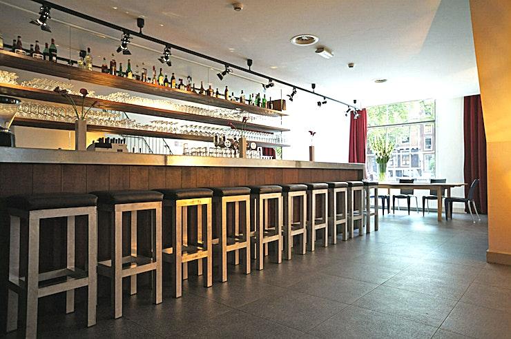 Cafe **Het cafe in de Rode Hoed is een perfecte locatie voor een teamevenement in Amsterdam.**   De unieke locatie in het hart van Amsterdam aan de historische UNESCO World Heritage grachten maakt van de Rode Hoed een perfecte locatie voor elk type evenement: van bestuursvergaderingen tot prijsuitreikingen. Het gebouw dateert uit de 17e eeuw, toen het diende als een kerk. Tegenwoordig staat de Rode Hoed bekend als een plek voor maatschappelijke debatten, symposia, literaire en muzikale bijeenkomsten, evenals een multifunctionele evenementenlocatie. De prachtige Oosterhuiszaal, samen met 5 andere sfeervolle kamers, maakt de Rode Hoed perfect voor conferenties met breakout-sessies, zakelijke evenementen en gala-avonden. De sfeer van een oude kerk in combinatie met het authentieke interieur en state-of-the-art technische faciliteiten zullen uw evenement extra speciaal maken.