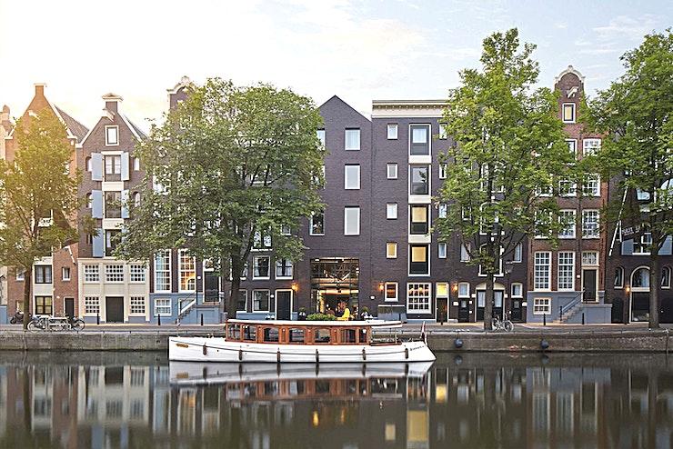 Saxenburg Room **De Saxenburg Room in Pulitzer Amsterdam is een multifunctionele ruimte.**   Het Saxenburg House is het meest weelderige herenhuis van Pulitzer. Kom in stijl aan via de eigen ingang op de Keizersgracht. De indrukwekkende salon beschikt over een geschilderd plafond, een grote kroonluchter en een uitzicht op de tuin die allemaal samenwerken om u terug te voeren naar een gouden tijdperk van gratie en pracht.  Sinds de Nederlandse Gouden Eeuwen vormen de grachtenpanden van Amsterdam het decor voor bloeiende creativiteit, handel en ontmoetingen. Pulitzer Amsterdam houdt deze traditie levend en biedt de perfecte locatie voor uw vergaderingen en evenementen.  Ontmoet typisch Nederlandse elegantie in een ingewikkeld doolhof van 25 verbonden grachtenpanden uit de Gouden Eeuw. Deze verborgen buurt beschikt over intieme kamers, rustige binnentuinen, vergader- en evenementenruimtes, een tuincafé, een hotelbar en een restaurant dat eenvoudige maar prachtig bewerkte gerechten serveert.  Pulitzer Amsterdam is een unieke mix van luxe, traditioneel en modern Nederlands vakmanschap verborgen tussen de iconische grachten van de stad.