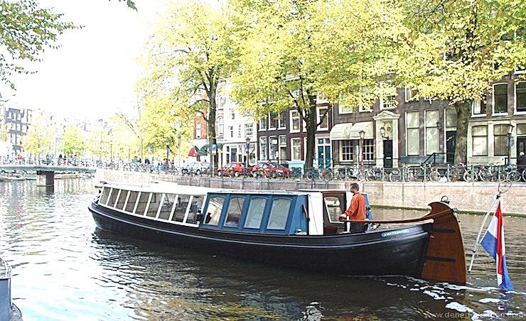 """JACOB VAN LENNEP **Jacob Van Lennep is een grote boot voor een klassieke rondvaart in Amsterdam voor maximaal 40 personen.**   De """"trekschuit"""" is één van de meest interessante soorten boten in de Nederlandse geschiedenis. Oorspronkelijk hadden deze boten geen motor en werden ze naar voren geschoven door middel van een ingenieus systeem van palen, touwen en paarden die op paden langs de rivier liepen. Dit werd een geavanceerd systeem met verschillende schema's en routes voor het vervoeren van personen en goederen in Nederland en was mede verantwoordelijk voor de late invoering van het spoorwegsysteem."""