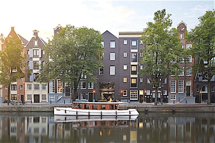 Merchant Room 2 **Merchant Room 2 is een blauwgetinte vergaderruimte in Pulitizer Amsterdam met een prachtig uitzicht op de gracht, perfect voor uw volgende vergadering.**  De diepe en weelderige Haagse blauwe kleur brengt een nobele sfeer in de kamer en omlijst het kanaal als het middelpunt van de ruimte.  Pulitzer Amsterdam is een unieke mix van luxe, traditioneel en modern Nederlands vakmanschap verborgen tussen de iconische grachten van de stad.