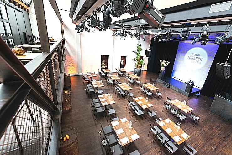 Grand Theater Hall **Het TOBACCO-theater is een unieke historische ruimte die te huur is voor uw volgende privé- of bedrijfsevenement.**   Je zou het niet verwachten als je door de kleine straat Nes loopt, de culturele hoofdstraat van Amsterdam. Een indrukwekkend hoge kamer van 200 m² (meer dan 2000 vierkante voet), gemaakt van staal en ruw wit gips. Industrieel, fris, stevig en met een duidelijke liefde voor design en geschiedenis.   Bij aankomst is het eerste wat u opvalt de bar in industriële stijl en het stalen balkon. Dankzij de historische sheddaken wordt het theater gevuld met daglicht. Je krijgt een kleine en zonnige glimp te zien van de rijke geschiedenis van het oude tabaksveilinghuis. De kamer is uitgerust met automatische dimmers en een uniek verlichtingssysteem, waarbij de schuine plafonds en de ruwe witte gipswanden theatraal en prachtig verlicht zijn.   Deze geheime locatie in het hart van Amsterdam is het toneel geweest voor vele geweldige theaterdiners, internationale productpresentaties en muziekpresentaties, congressen, evenementen en liefdevolle theatervoorstellingen.