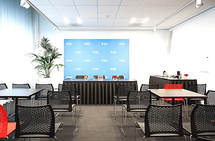 """Van der Poelzaal I **Een andere grote bijeenkomstruimte te huur in Den Haag is de Van der Poelzaal 1 in Nieuwspoort.**  Van der Poelzaal I en II, grenzend aan en teneinde De Poten, zijn de kleinste zalen Nieuwspoort. De ruimtes zijn, afzonderlijk of in combinatie, geschikt voor iedere denkbare bijeenkomst van 2 tot maximaal 60 personen.   Nieuwspoort is verbonden aan het gebouw van de Tweede Kamer, in het centrum van Den Haag. De koninklijke stad van Nederland. Elke kamer kan afzonderlijk worden gehuurd, maar combinaties zijn ook mogelijk tot een capaciteit van bijna duizend bezoekers.    Nieuwspoort heeft zelf alle kennis en expertise in huis voor het begeleiden van elk type evenement, zowel organisatorisch als technisch. In Nieuwspoort kunt u altijd een kamer kiezen die exact overeenkomt met de aard en de grootte van uw evenement.    De verschillende ruimtes hebben de allure die past bij Nieuwspoort, elk met een eigen uitzicht, variërend van de prachtige binnentuin en de Lange Poten tot de 24 meter hoge """"Statenpassage"""" van de Tweede Kamer. Je kunt natuurlijk altijd de indeling van de ruimtes aanpassen aan het karakter van je evenement. Het hele gebouw of de bar / het restaurant huren is alleen mogelijk in het weekend. """""""