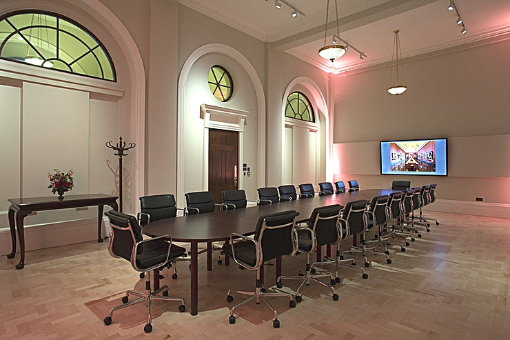 """The Wilkins Boardroom **The Wilkins Boardroom is a state-of-the-art boardroom for hire at The National Gallery.**  This remarkable Space offers all the conveniences of a modern meeting room, located along the prestigious Director's Corridor and accessible from our West Door entrance.   Seating 16 for a seated dinner on one long table, this bright and modern space has fantastic audio-visual facilities, air conditioning and natural lighting.   This room is great for presentations to intimate evening entertaining for receptions and dinners.   Included in the venue hire fee is:  70"""" NEC LCD screen Installed PC, with audio system. Laptops supported Dropdown screen Dedicated Event Co-ordinator"""