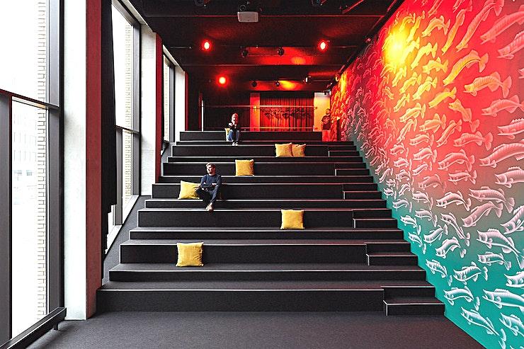 Auditorium **Het Auditorium in The Student Hotel Eindhoven is een prachtige vergaderruimte en is nu beschikbaar voor verhuur.**   Organiseer uw volgende externe vergadering direct tegenover het centraal station van Eindhoven, zodat uw collega's de locatie gemakkelijk kunnen vinden. Boek een netwerkevenement, een innovatieve breakout-sessie, een eendaagse cursus in onze klas, een verzorgde werklunch of diner en cocktails met een gewaardeerde klant in ons bekroonde designhotel.    Stap uit het treinstation van Eindhoven en u ziet de locatie direct. Aan de overkant van het station ligt dit full-service hotel met 400 kamers en een co-living gemeenschap voor studenten, reizigers en professionals. Het hotel heeft ook een restaurant en bar met 250 zitplaatsen, The Commons, die een hotspot voor fijnproevers in Eindhoven aan het worden is.