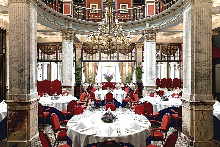 Lounge and Restaurant Anyone that cruises through the lobby of Hotel Des Indes, will be transported to another era.   The monumental entryway, which was the location where the horse-drawn carriages with visitors entered the building, exudes a rich history.  The opulent design of the Lounge / Restaurant, that is well suited to the prestige of this iconic hotel, is certainly chic while at the same time being quite warm and inviting. The marble columns, the chandelier and the sweeping stately staircases spin the tale of the 19th-century urban town palace of Baron Van Brienen, which would later transform into the luxurious Des Indes Hotel.  From the floor overlooking the foyer, nicknamed the Rotary, you have a wonderful view of the Lounge / Restaurant while leaning upon the balustrade. This is the location the baron used to greet his newly arrived guests.