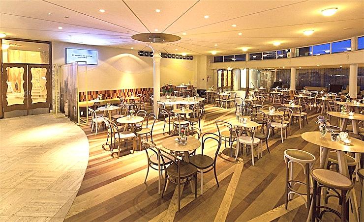 Theatercafe **Theatercafe van Kunstmin is een stijlvolle evenementenlocatie in Dordrecht.**  Het theatercafé in Schouwburg Kunstmin heeft een moderne en gastvrije sfeer. Gelegen in het semi-circulaire extensie die architect Sybold van Ravesteyn heeft toegevoegd aan het theater in de jaren dertig van de vorige eeuw.  Het café heeft ramen rondom, waardoor de ruimte licht en ruim is.  Hoogtepunten zijn onder andere de vloer, de strook parket in verschillende tinten, de moderne witte balk en de Thonet stoelen in pasteltinten.